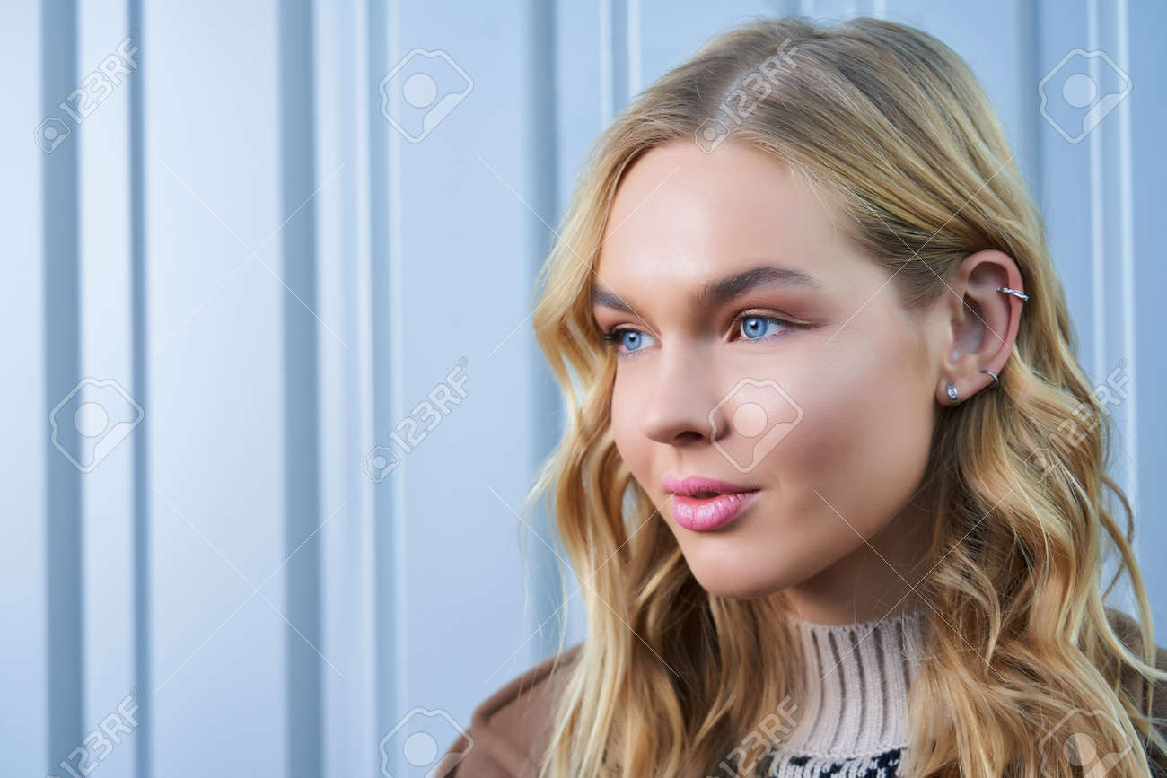 portrait of a blonde girl with blue eyes on a silver background - 169021378