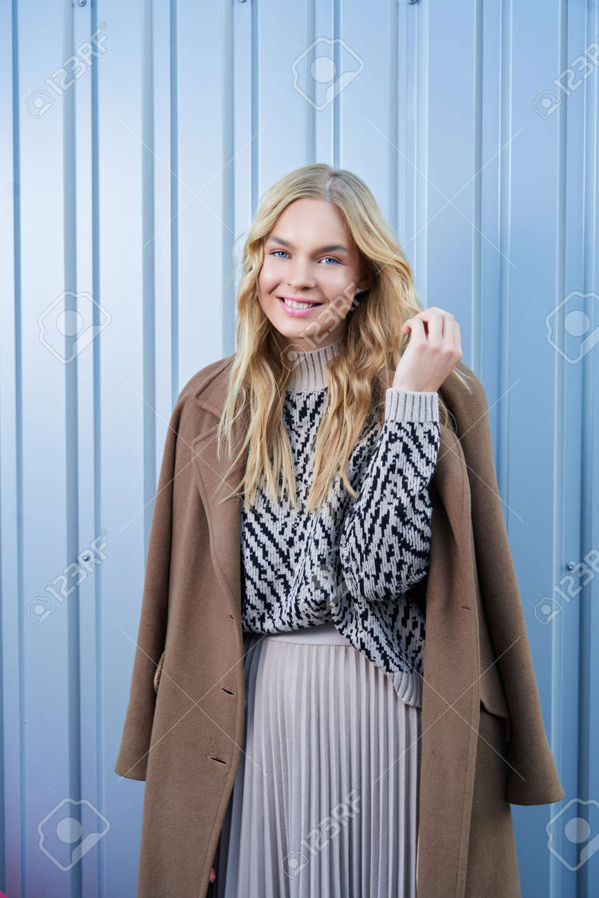 Stylish cute young blonde woman in seasonal fashionable beige coat posing near silver metal wall outdoors. Fashionable girl model in the city. - 169021397