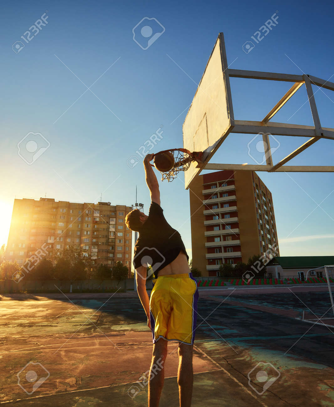 A young basketball player driving to the hoop for a slam dunk. - 169021409