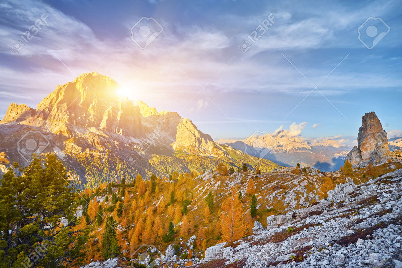 View of Tofane mountains seen from Falzarego pass in an autumn landscape in Dolomites, Italy. Mountains, fir trees and above all larches that change color assuming the typical yellow autumn color - 173010816