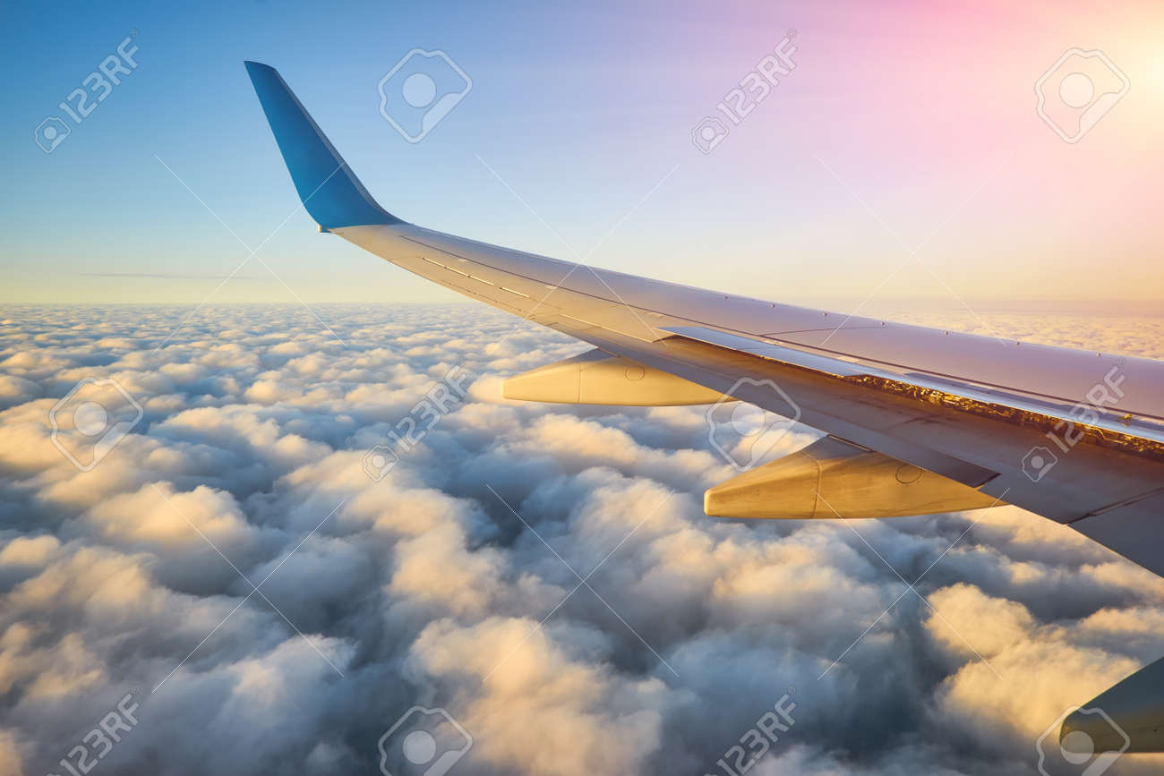 Spectacular view of a sunset above the clouds from airplane window - 173010928