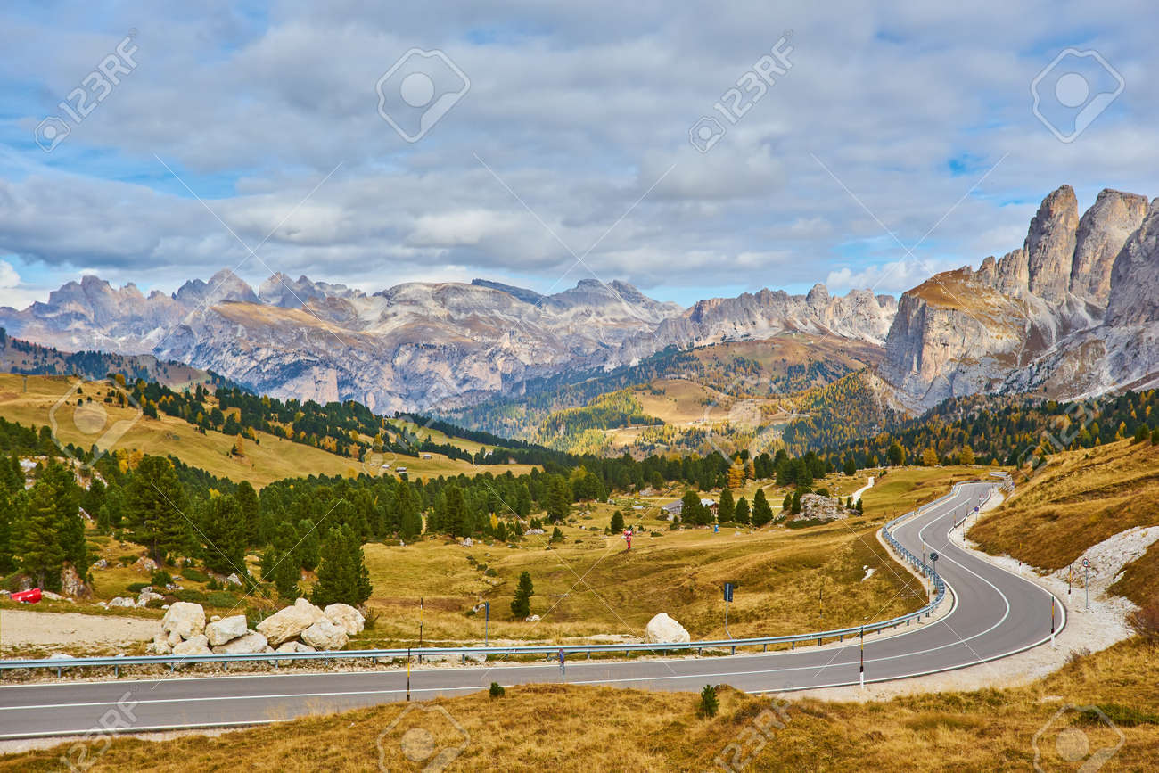 View of winding road. Asphalt roads in the Italian Alps in South Tyrol, during autumn season. Autumn scene with curved road and yellow larches from both sides in alp forest. Dolomite Alps. Italy - 173011153
