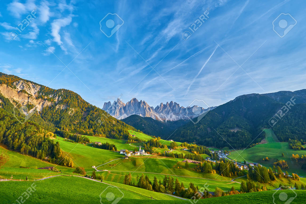 Amazing autumn scenery in Santa Maddalena village with church, colorful trees and meadows under rising sun rays. Dolomite Alps, South Tyrol, Italy. - 172909457