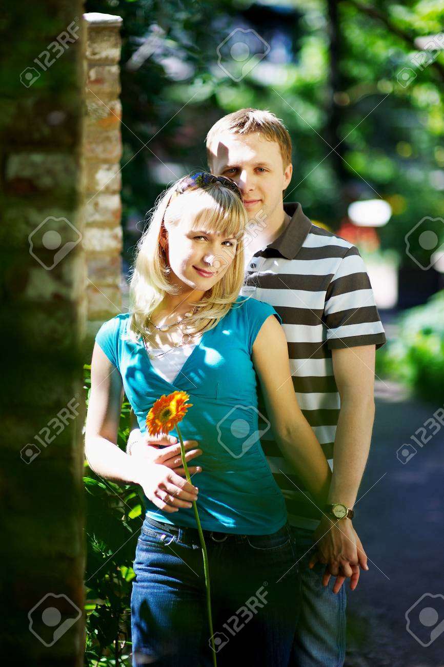 Lovers man and woman with gerbera flower in romantic date in park Stock Photo - 10697888