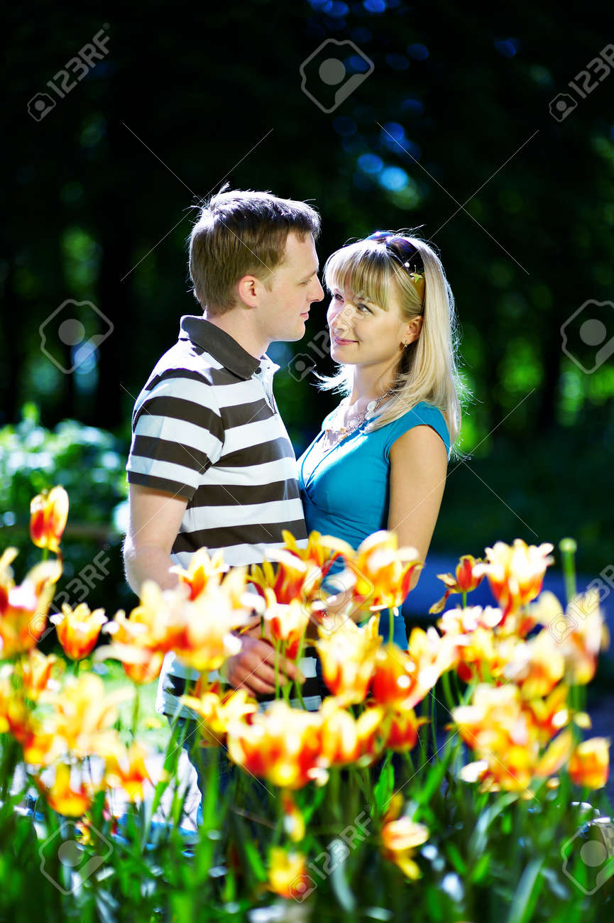 Lover man and girl among red yellow flowers in spring park Stock Photo - 10697893