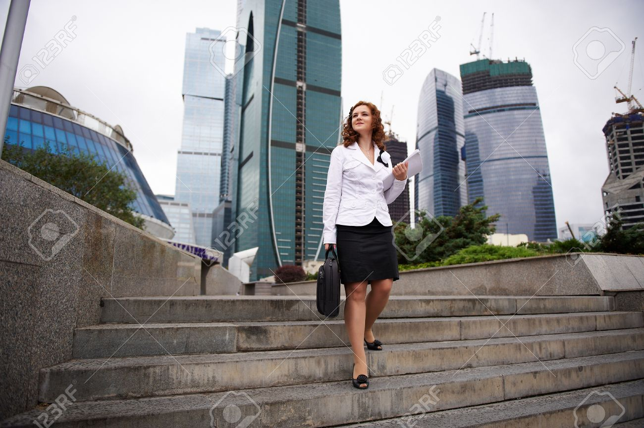 Young business woman descends the stairs to the street Stock Photo - 11559170