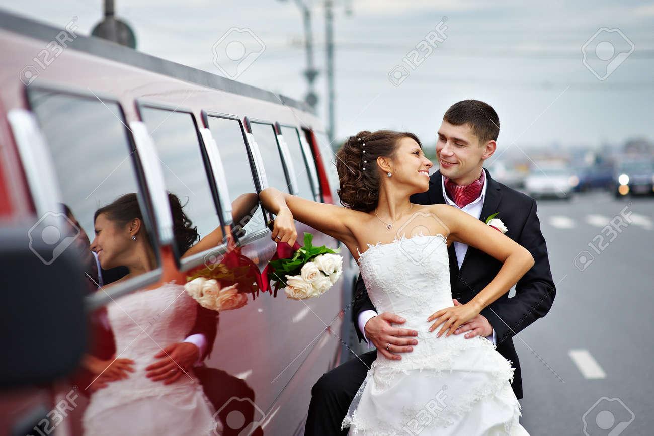 Happy bride and groom near wedding limo on walk Stock Photo - 13901130
