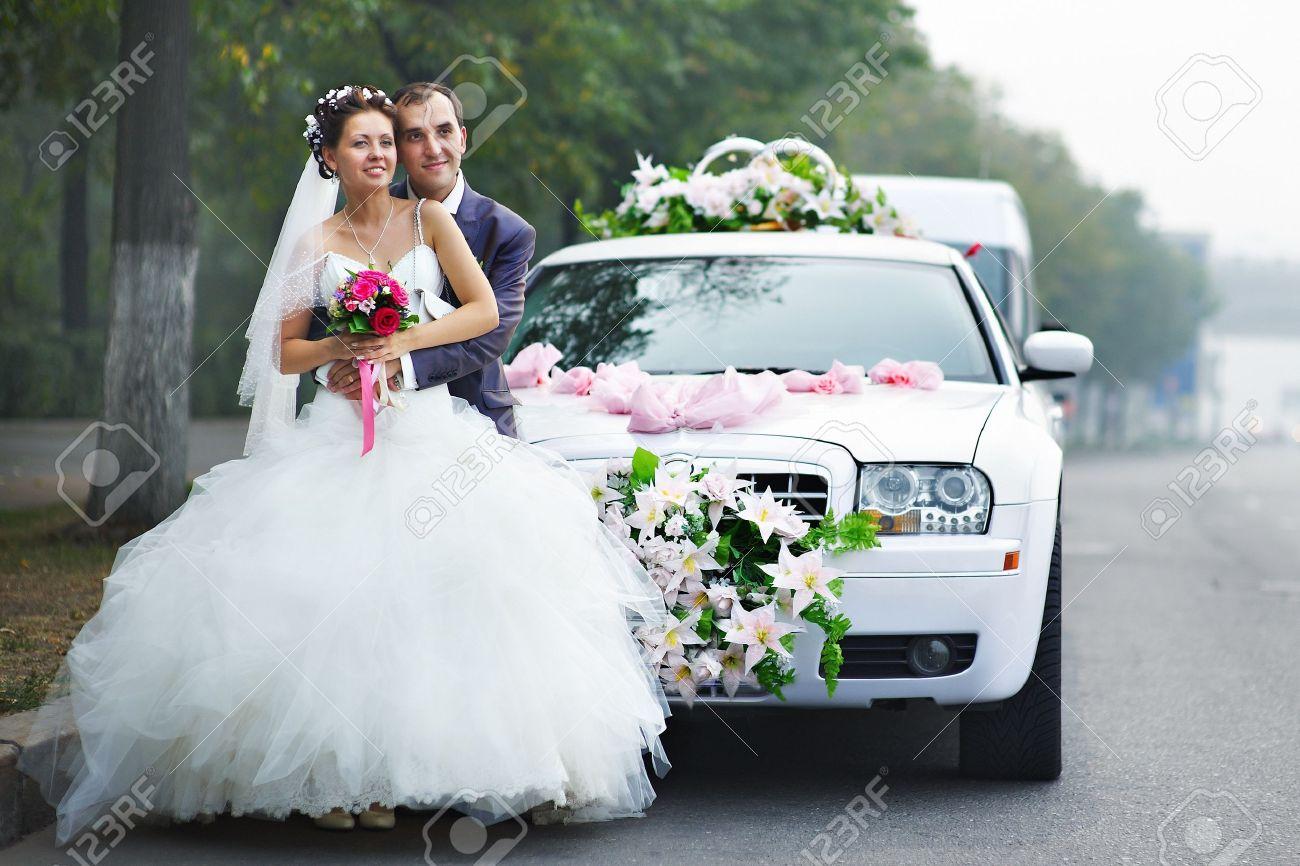 Happy bride and groom near wedding limo - 13997133