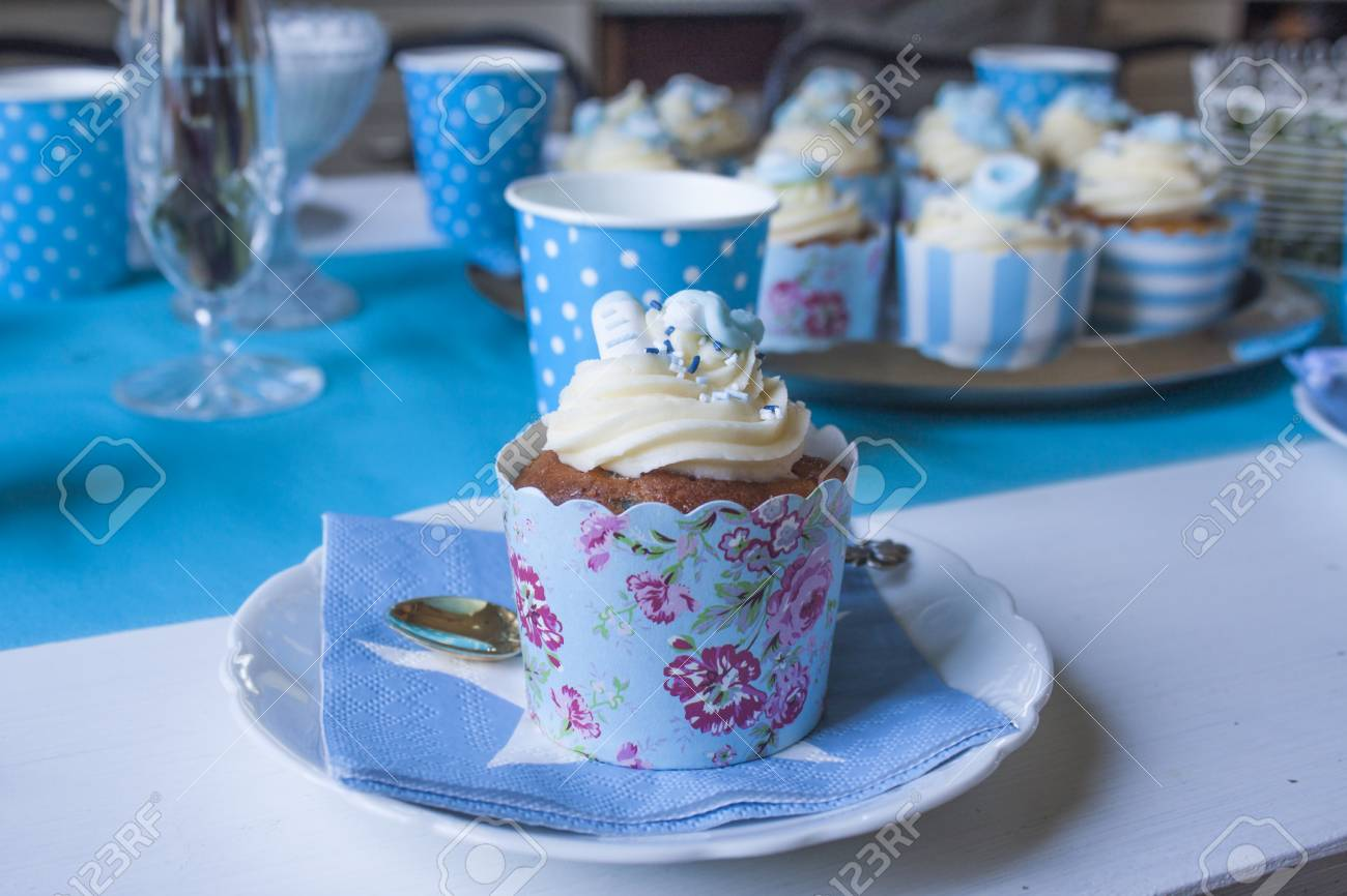 One Baby Shower Cupcake In Front Of Others At A Blue Table Stock