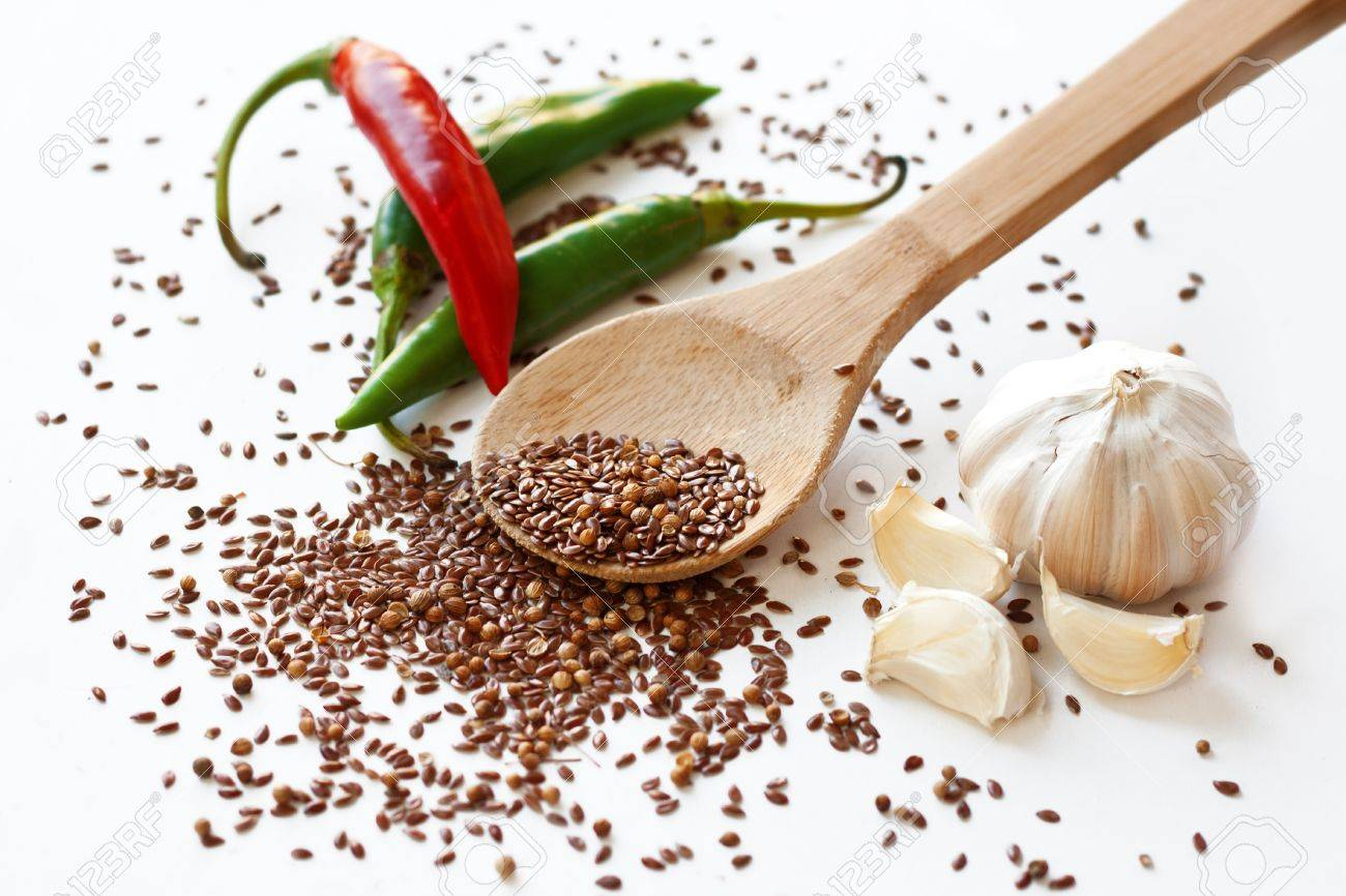 Cayenne peppers, flax seeds, coriander and garlic on white background Stock Photo - 15564225