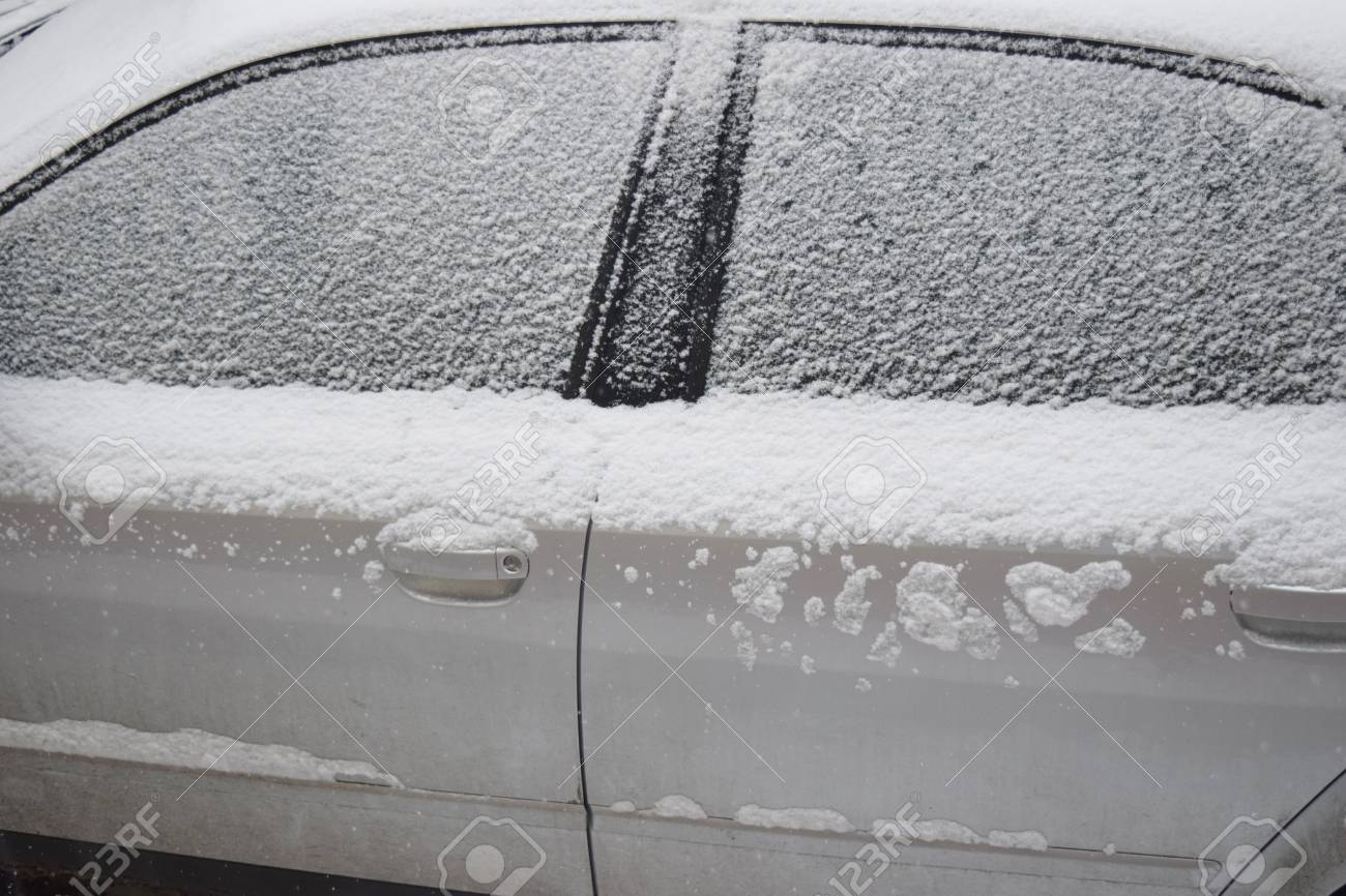 Car covered with white snow while still snowing in Medias, Romania. Stock Photo - 51356099