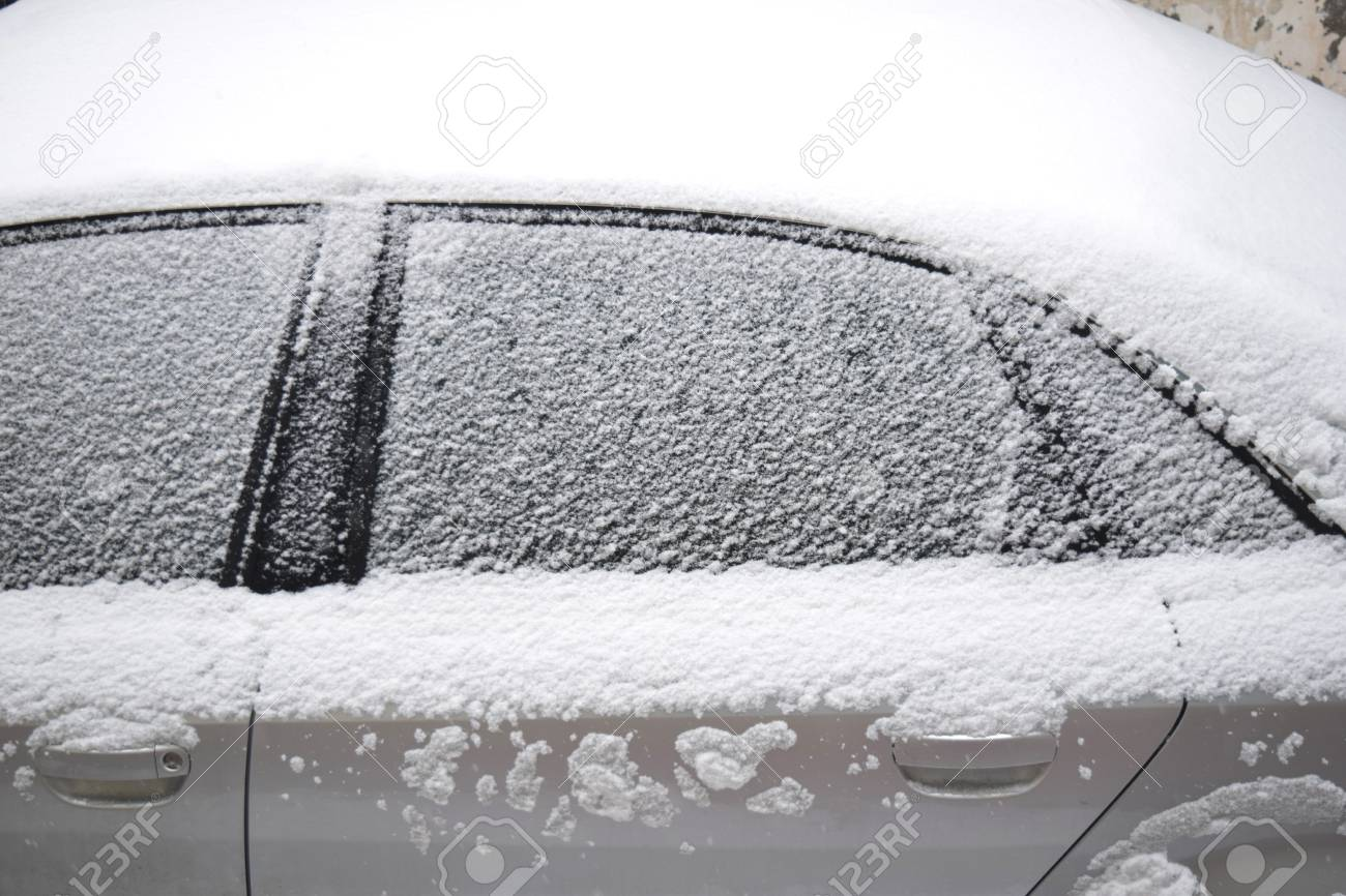 Car covered with white snow while still snowing in Medias, Romania. Stock Photo - 51356109