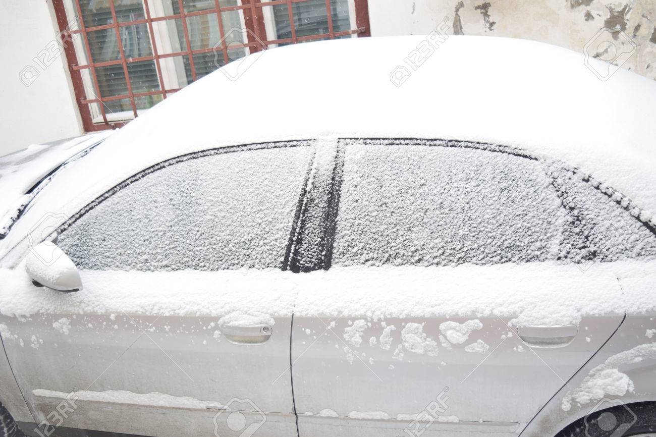 Car covered with white snow while still snowing in Medias, Romania. Stock Photo - 51356066