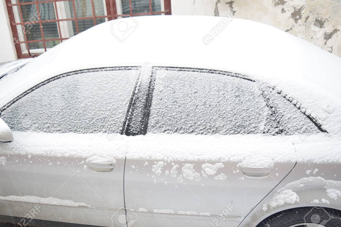 Car covered with white snow while still snowing in Medias, Romania. Stock Photo - 51356111
