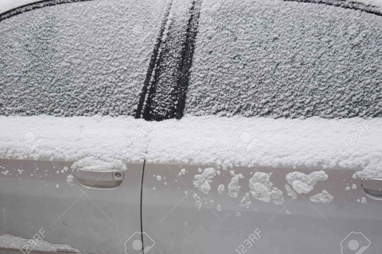 Car covered with white snow while still snowing in Medias, Romania. Stock Photo - 51356100