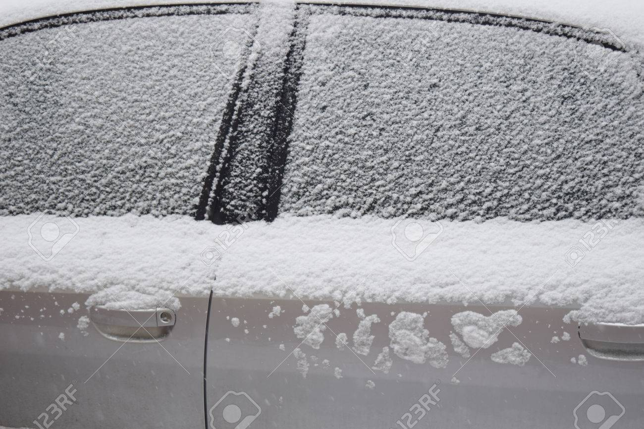 Car body part covered with white snow while still snowing in Medias, Romania. Stock Photo - 51356103