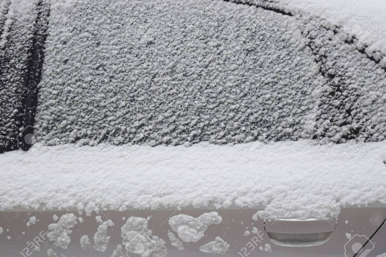 Car body part covered with white snow while still snowing in Medias, Romania. Stock Photo - 51356088