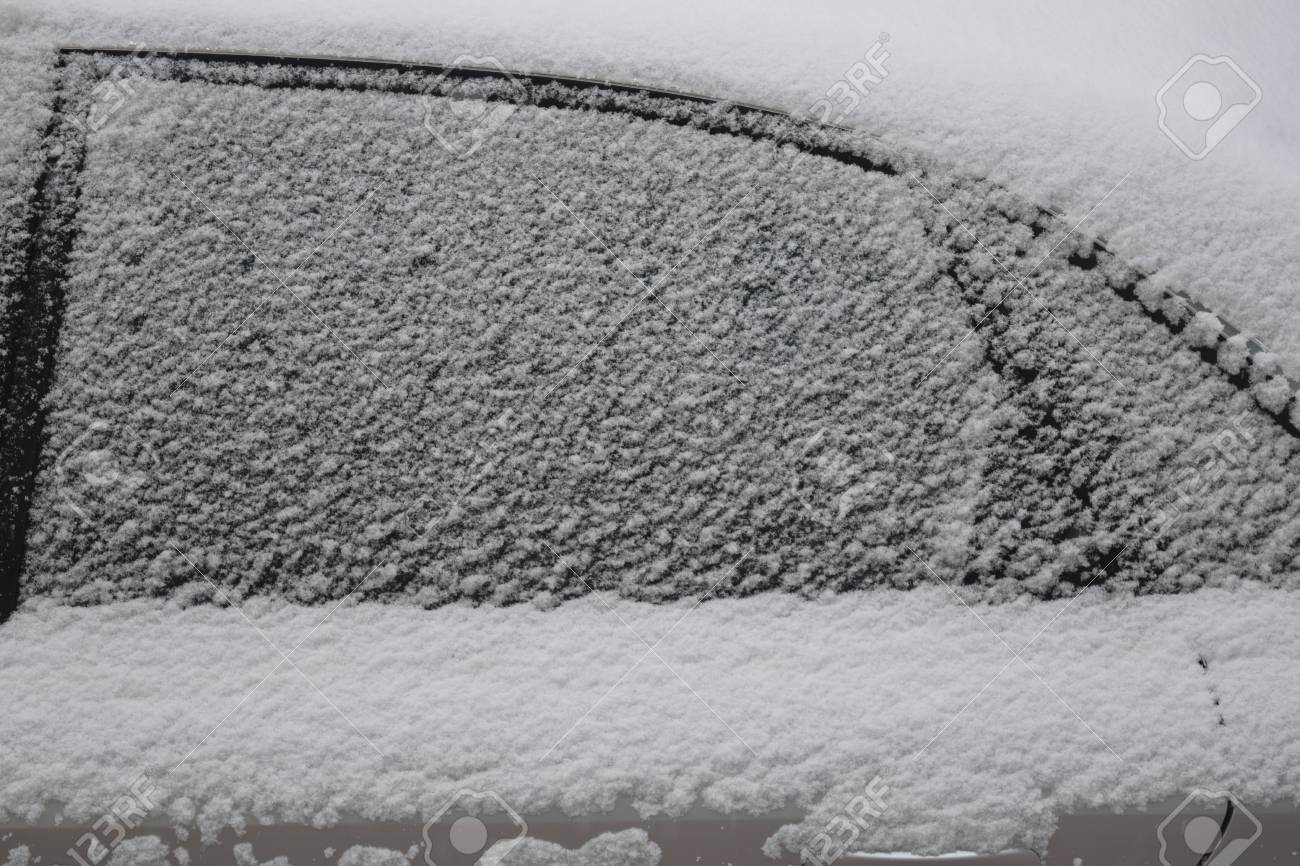 Car body part covered with white snow while still snowing in Medias, Romania. Stock Photo - 51356107
