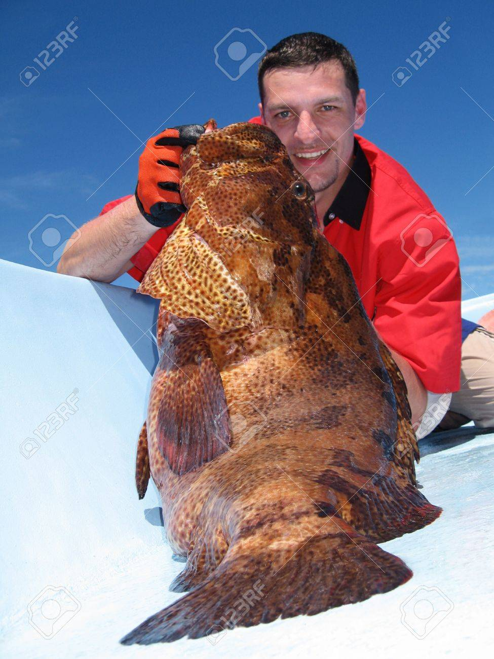 Happy  fisherman holding a grouper Stock Photo - 16661006