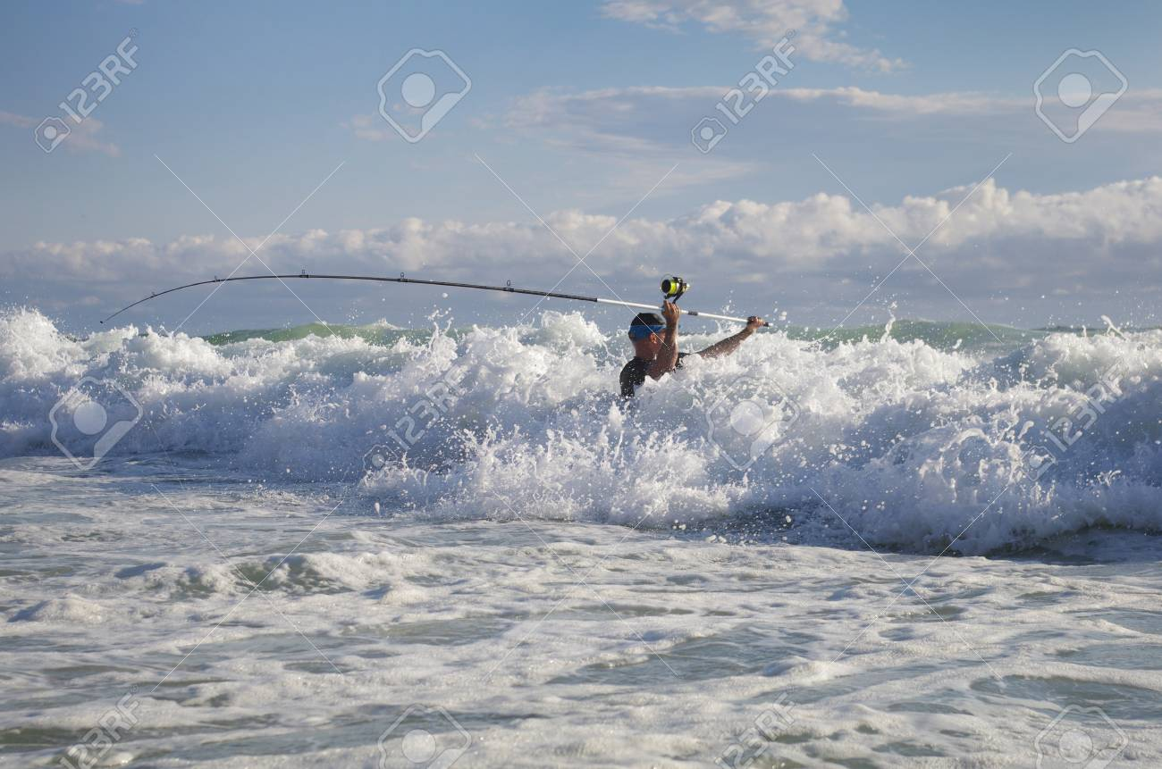 Surf fisherman into the waves. Surf casting fishing - 122087666