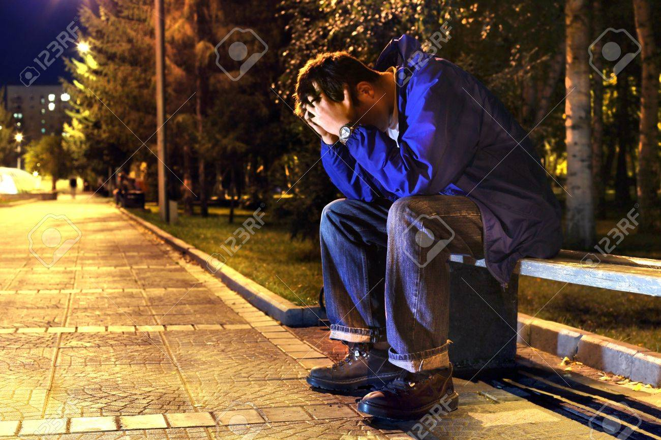 sad and lonely teenager with hidden face sitting in the night park Stock Photo - 11221158