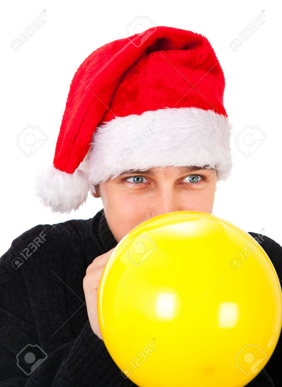 f293c6a9b Young Man in Santa Hat inflate a Yellow Balloon Isolated on the..