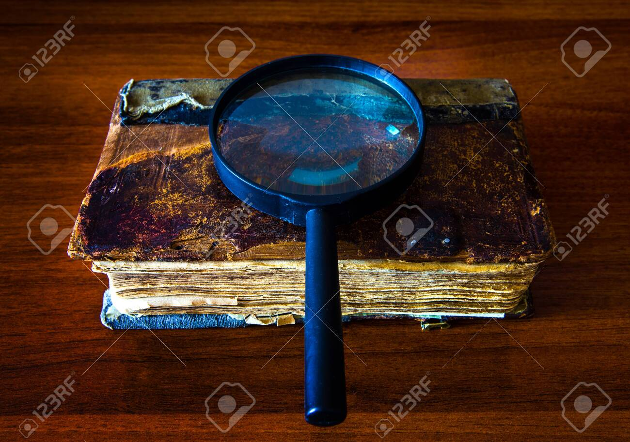 Old Book with a Magnifying Glass on the Table closeup - 121335860