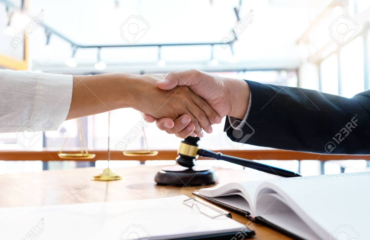 Lawyer or judge with gavel and balance handshake with client or customer about agreement how to use arbitration handshake - 120472933