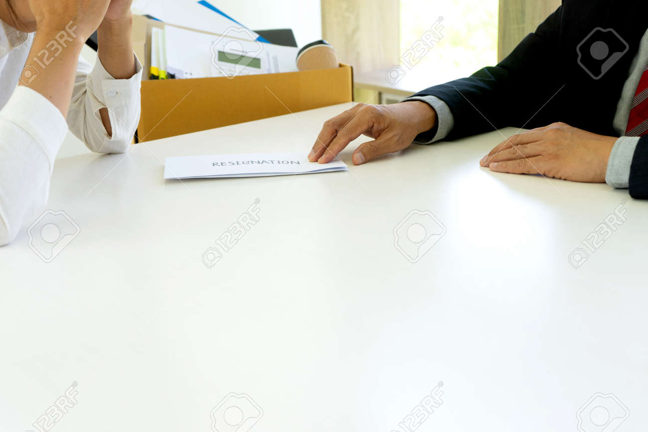 The boss handed a resignation letter of dismissal to the grieving employee on the desk. - 169228090
