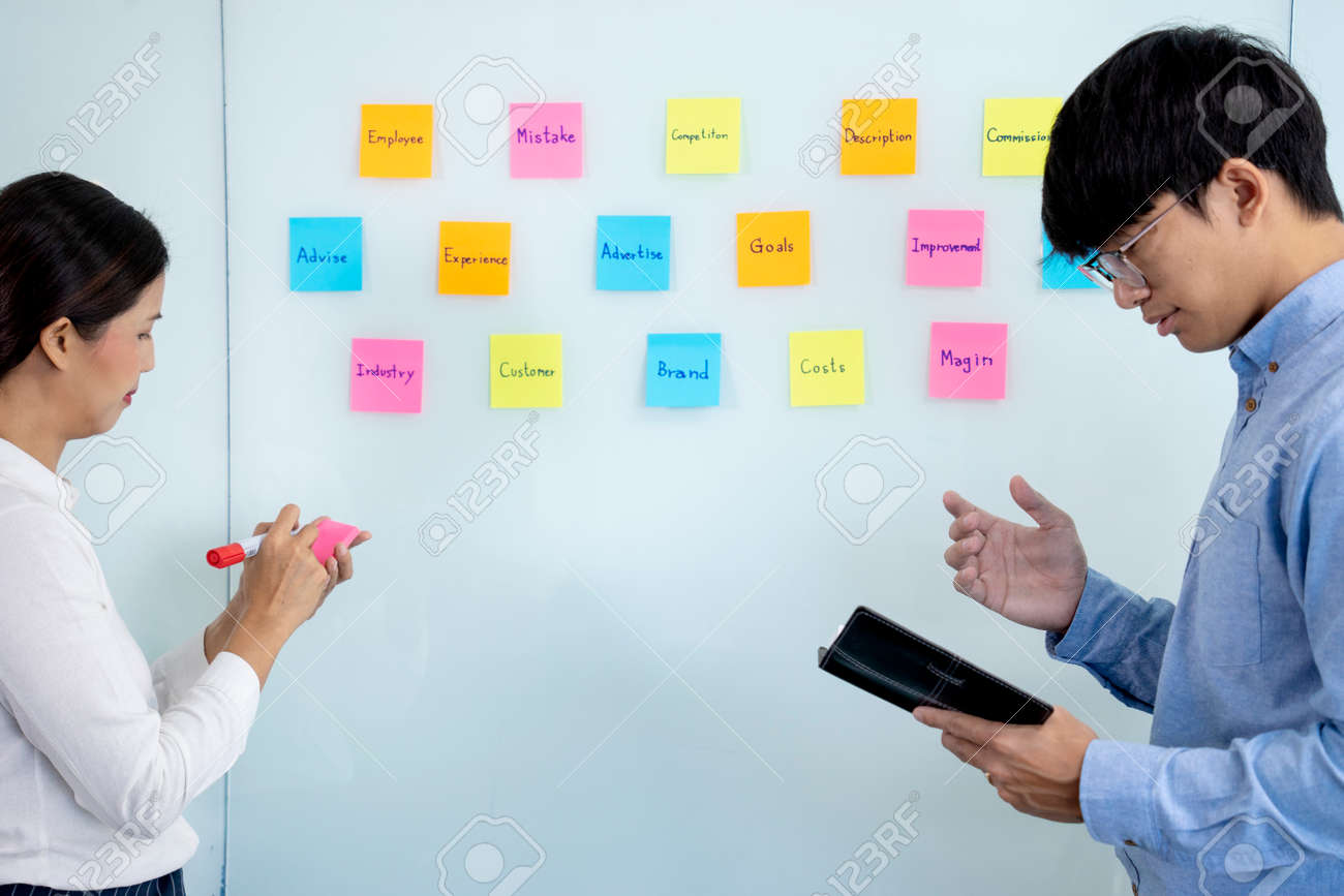 Businessmen and woman are standing He giving advice and brainstorming for Find an ideal and Write to notepad and stick it on the board. - 169229280