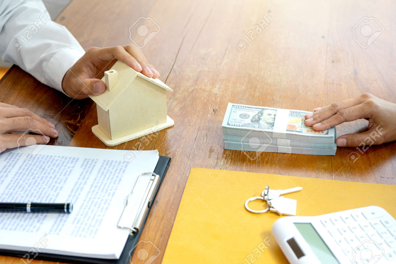 The businessman is handing the house keys to the contracted client and cash is being prepared for the real estate deal against Real estate business project. - 169228097