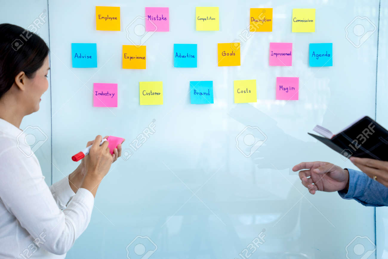 Businessmen and woman are standing He giving advice and brainstorming for Find an ideal and Write to notepad and stick it on the board. - 169229292