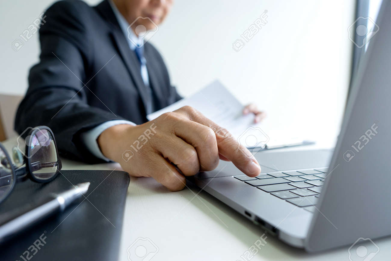 Smart businessman sitting happily thinking on a chair in the office his hand hold the pen with more copy space. - 169229296