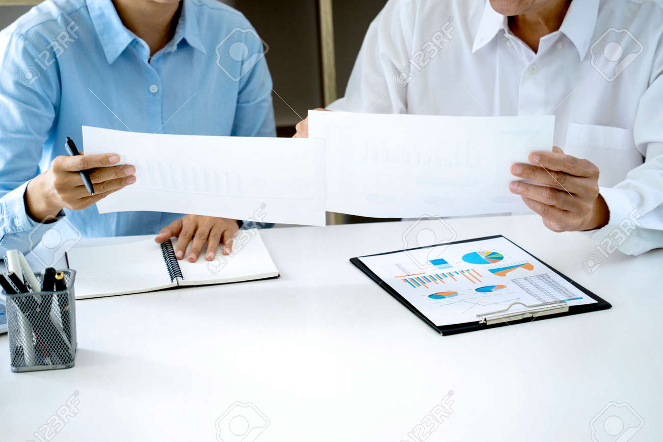 The businesswoman sit and look examined the documents the standing staff presented while working in the office. - 169229307