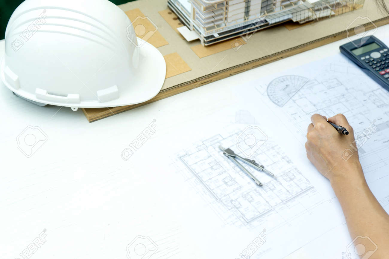 architects or engineer holding pen pointing equipment architects On the desk with a blueprint in the office building model and hat are on the table. - 169322411