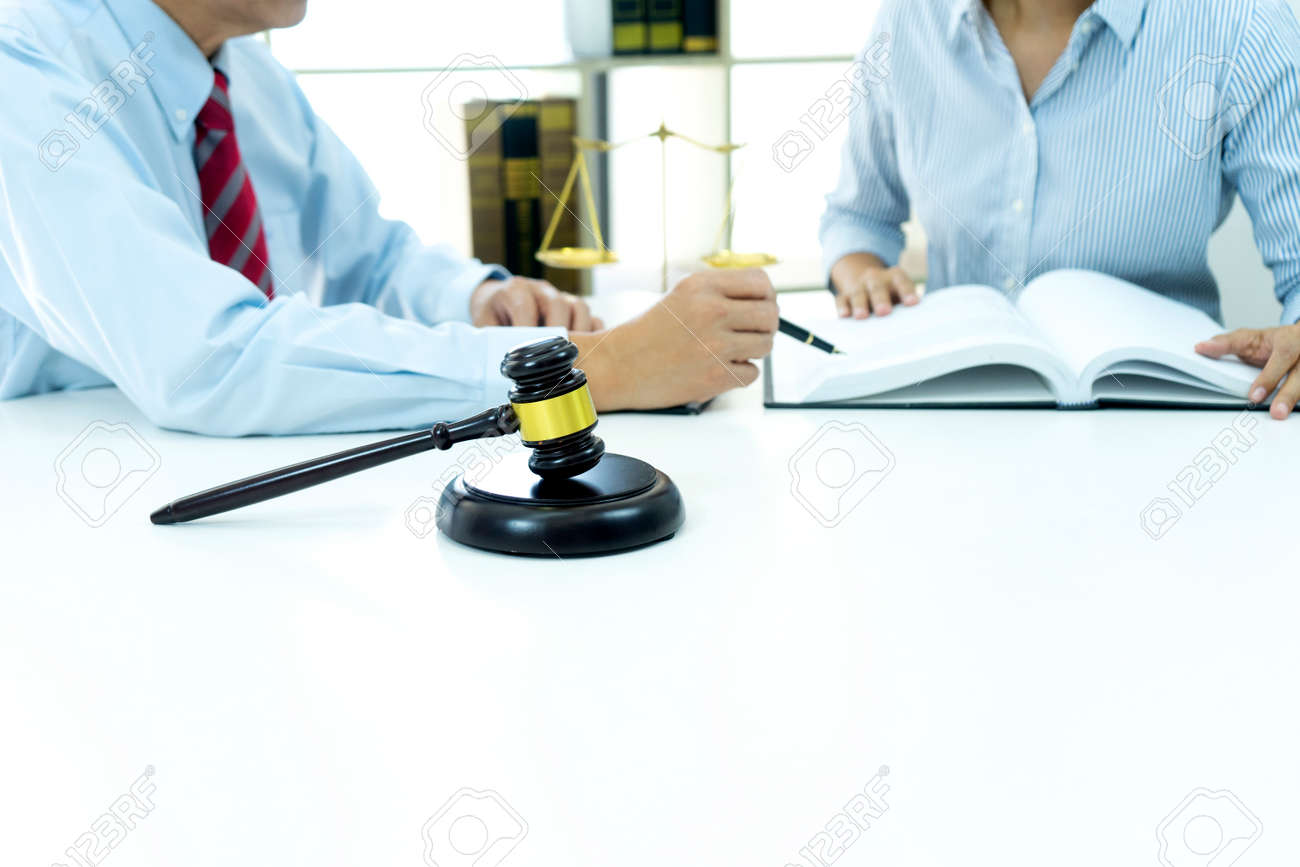 The businesswoman sit and look examined the documents the standing staff presented while working in the office. - 169322428