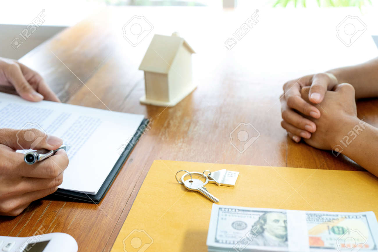 Sale representative or insurance broker offer house purchase contract to buy a house or apartment and give home key chain to customer - 169322434
