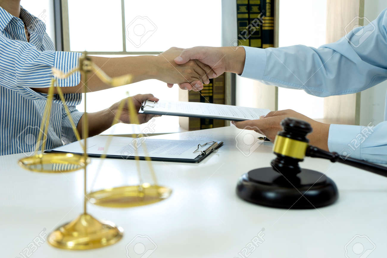 Two business people are handshake and exchanging a business contract deal in the law firm after finish meeting. - 169229761