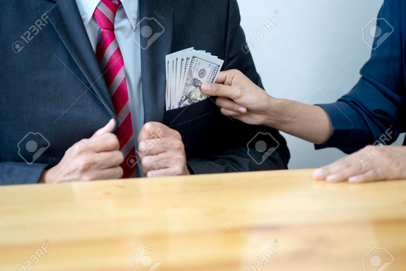 Businessmen or customers are putting money into the pocket of the officer's shirt to help them run the business bribe or corruption concept - 169229774