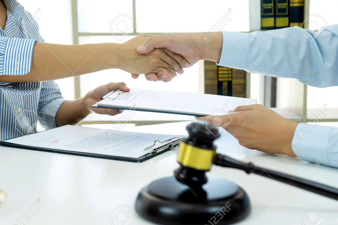 In the law firm, business people are exchanging contracts and shaking hands to congratulate on their success at work. - 169229776