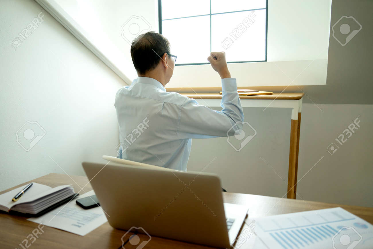Smart businessman sitting happily thinking on a chair in the office his hand hold the pen with more copy space. - 169229779