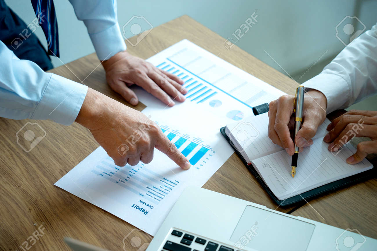 businessman point to the paper graph to tell staff team about the marketing plan - 169229938