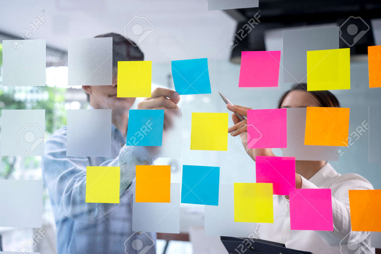 Businessmen and woman are standing He giving advice and brainstorming for Find an ideal and Write to notepad and stick it on the board. - 169229969