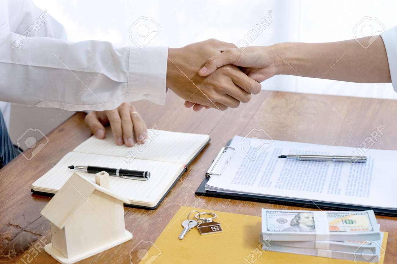 Sale representative or insurance broker handshake with customer after house purchase contract buy a house or apartment - 169230091