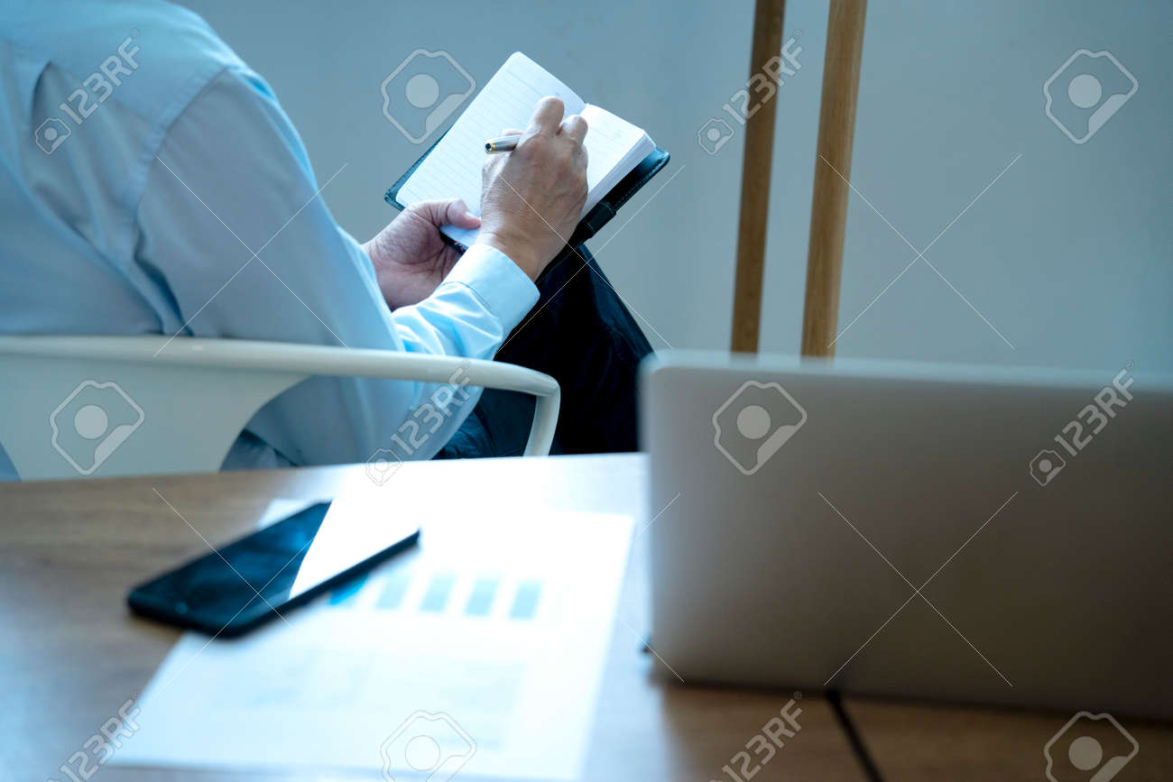 Smart businessman executive ceo or manager sitting thinking on a chair in the office his hand hold the pen with more copy space. - 169231315