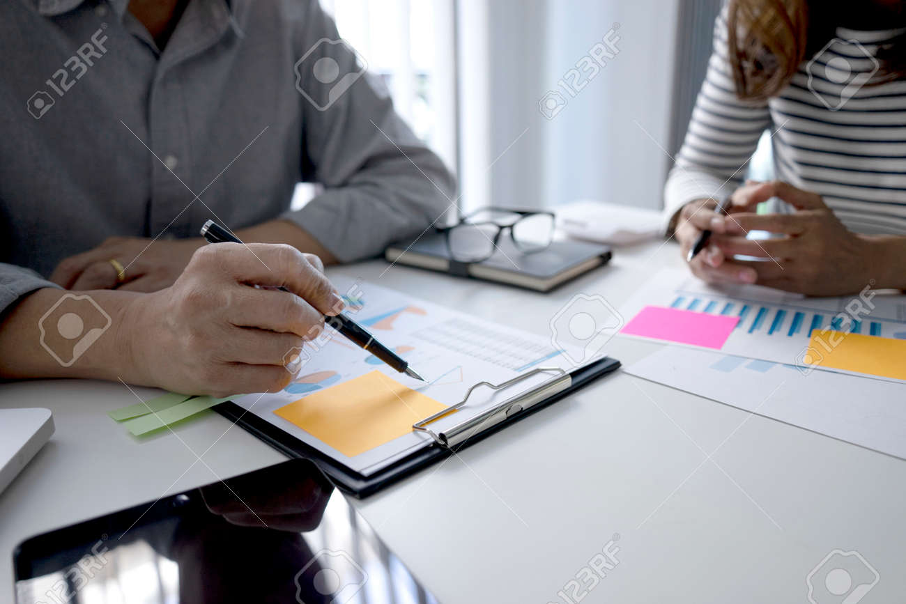The businesswoman sit and look examined the documents the standing staff presented while working in the office. - 169232001