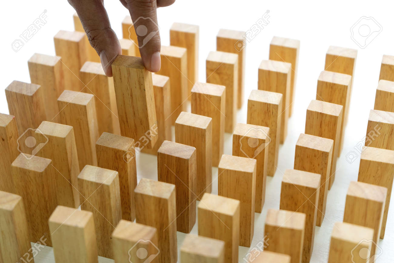 Young man holds the wood block in his hand to put it into the row to protect the domino effect business concept - 169232027