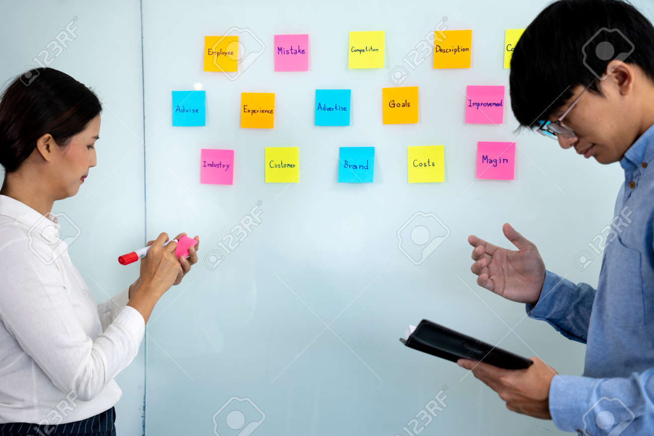 Businessmen and woman are standing He giving advice and brainstorming for Find an ideal and Write to notepad and stick it on the board. - 169231329