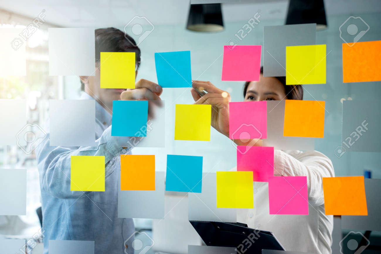 Businessmen and woman are standing He giving advice and brainstorming for Find an ideal and Write to notepad and stick it on the board. - 169232045
