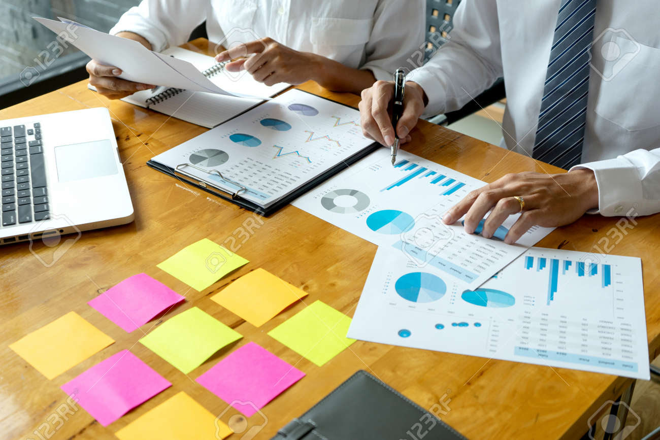 Business men and women are having a business plan consultation meeting by bringing information and graphs to study by putting notepads on the table to prepare to write idea - 169322642
